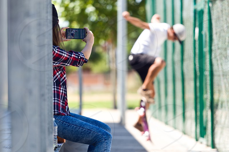 Young couple skateboarding in the street photo