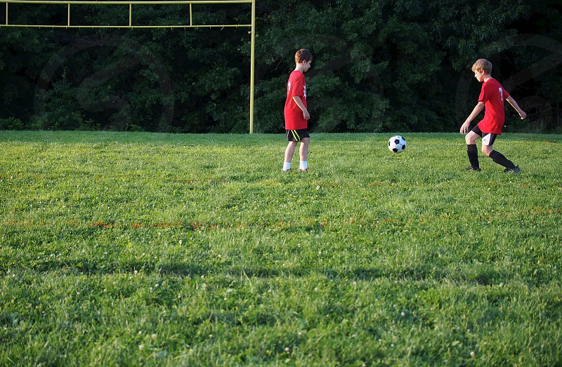 Two young boys playing soccer. photo