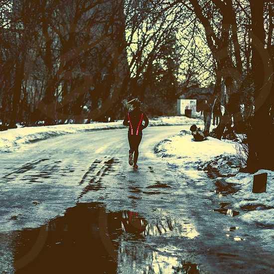 person jogging on wet road photo