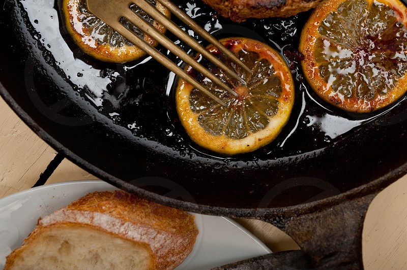 pork chop seared on iron skillet with lemon and spices seasoning photo