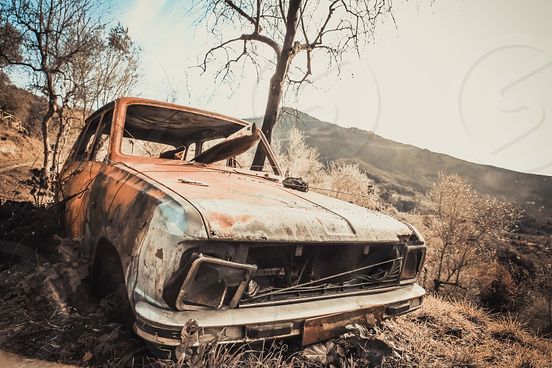 An old rusty and destroyed car abandoned in the nature photo