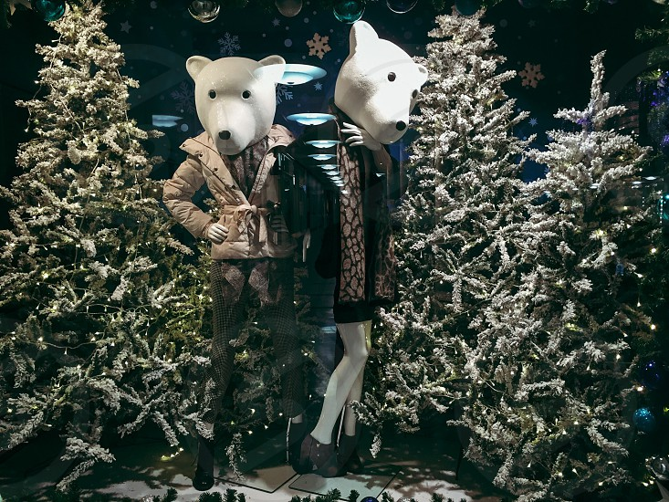 2 people wearing polar bear head mask beside trees photo
