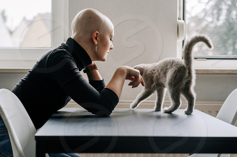 cancer patient plays with cat at home  photo