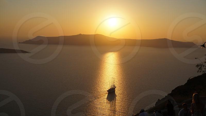 View of a boat in the Aegean Sea and the Santorini Caldera photo