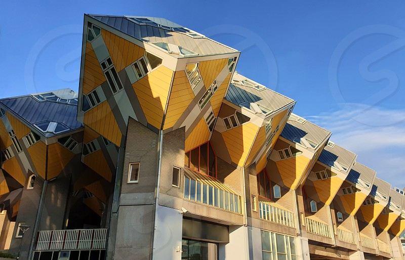 Cube houses under clear blue sky in Rotterdam the Netherlands. Representing a village where each house is a tree. A row of quirky yellow unusual cube shape architecture apartment block. photo
