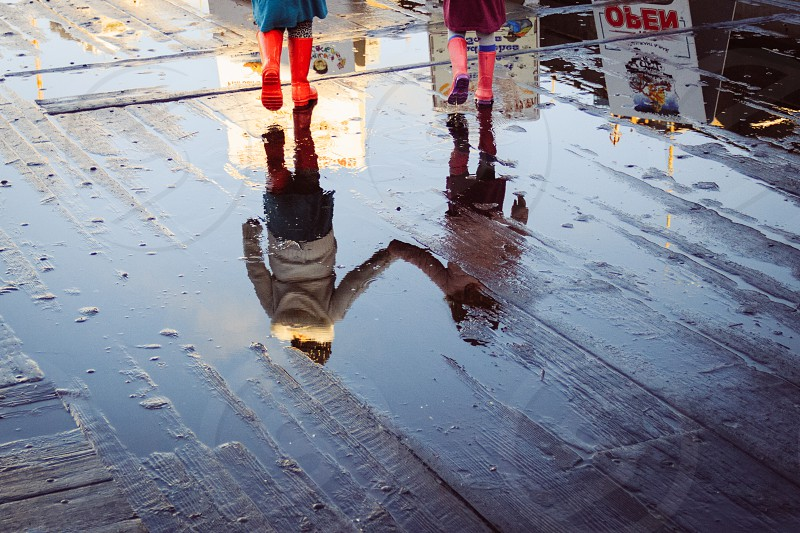 Best friends holding hands after rain reflecting in a puddle  photo