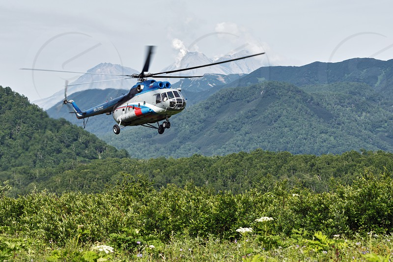 KAMCHATKA PENINSULA RUSSIAN FAR EAST - JULY 11 2014: A russian helicopter MI-8 with tourists flying in the forest on the background of mountains and volcano on sunny summer day. photo