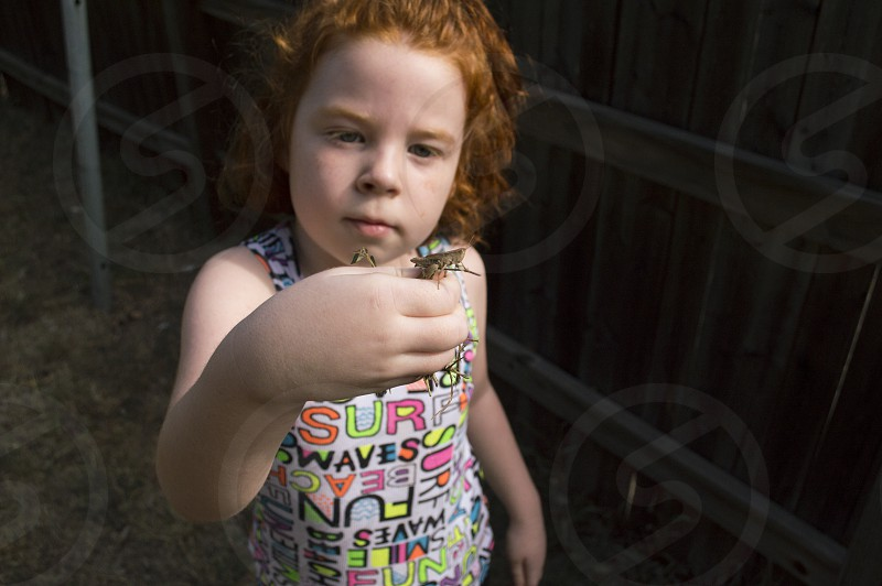 Young girl out exploring on a hike and looking with intense curiosity at a grasshopper she found and is holding. photo