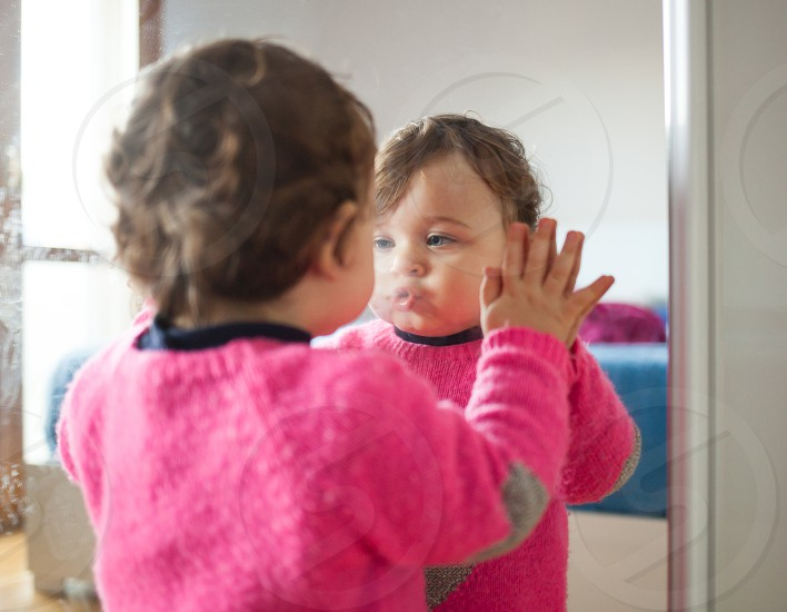 Toddler baby girl playing with mirror in the bedroom. photo