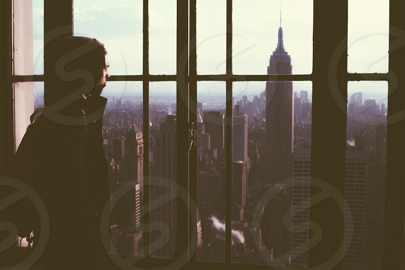 person by the glass window staring at empire state building photo