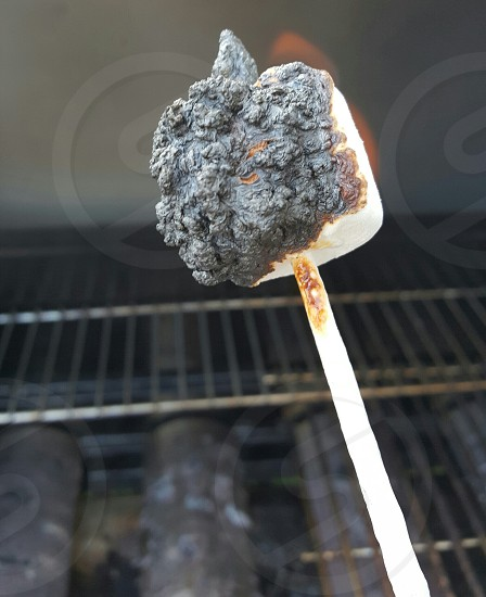 marshmellow on fire over grill photo