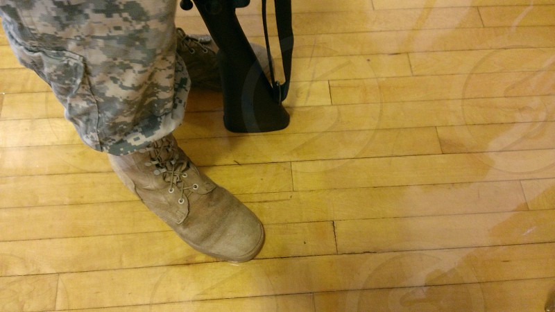 person wearing camouflage standing on wooden floor photo