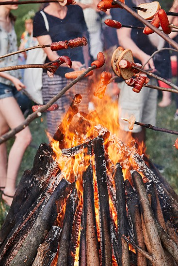 People roasting sausages and bread over a bonfire during picnic party on summer vacation day. Real people authentic situations photo