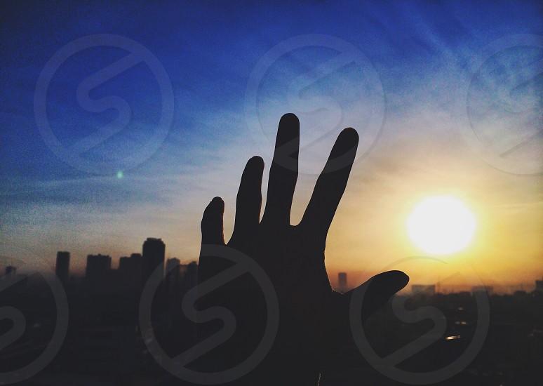 left hand reaching the sun photo
