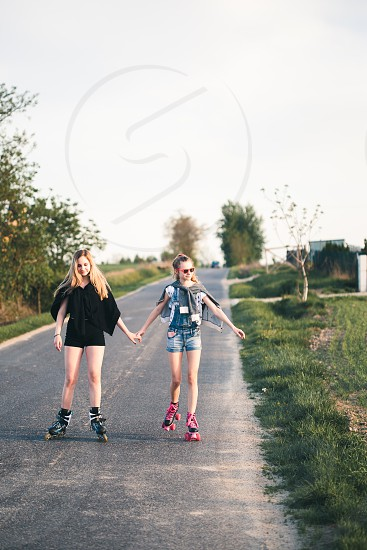 Teenage smiling happy girls having fun rollerskating spending time together on summer day photo