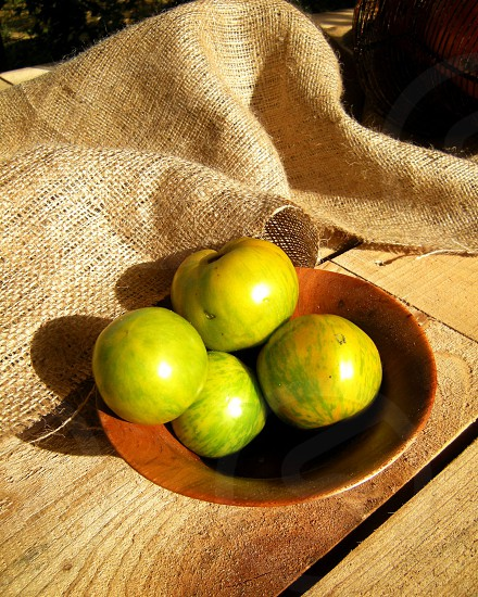 Green tomatoes in wooden bowl on wood with burlap photo