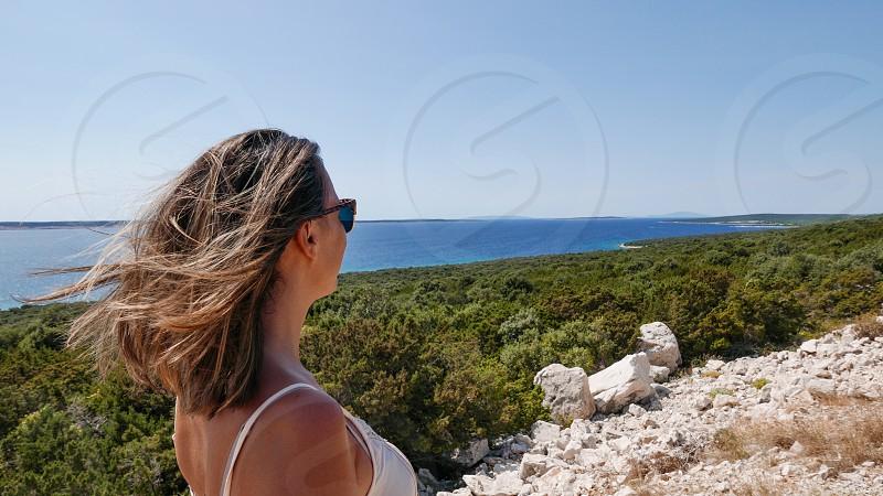Woman looking at the horizon at sea. Island of Pag Croatia. photo