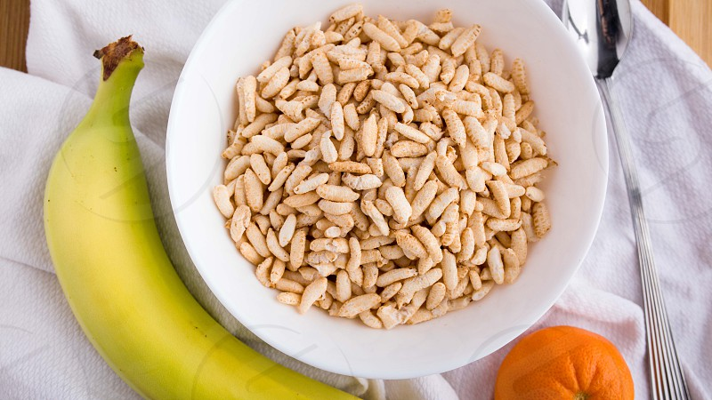 A well balanced breakfast is ready to be eaten. It includes a whole grain cereal a banana and an orange. photo