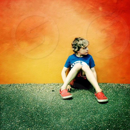 boy in blue round neck shirt wearing red shorts and crocs sandals sitting on floor photo
