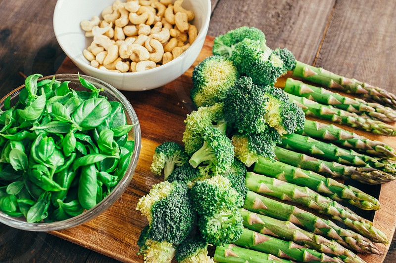 broccoli florets asparagus spinach and cashews on brown wooden cutting board photo