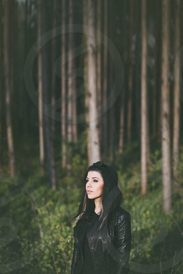 woman wearing a black leather jacket standing in the forest photo
