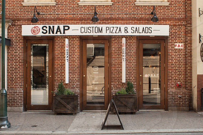 snap custom pizza and salads store with 3 wooden based clear glass door at daytime photo