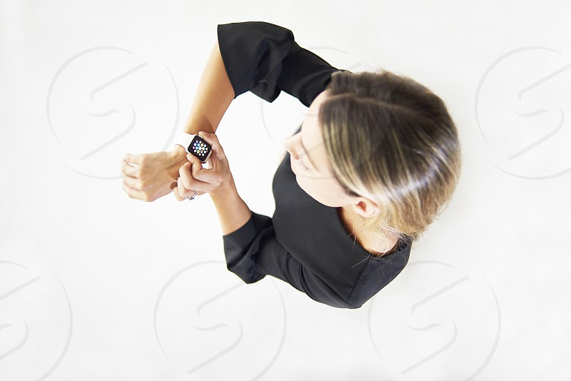 Top down shot of a caucasian woman in a studio looking at the screen of her smart watch photo