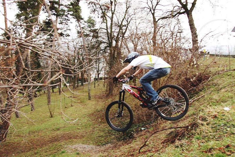 biker riding full suspension mountain bike on forest photo