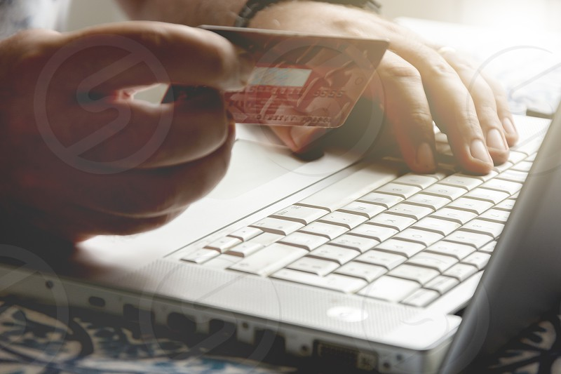 male hand holding a credit card during an internet payment transaction. Concept of e-commerce and online shopping. photo