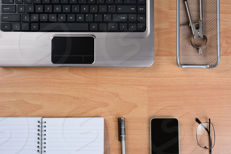 High angle view of a modern business desk with laptop cell phone pen paper glasses and other office items. Horizontal format with copy space in the middle.  photo