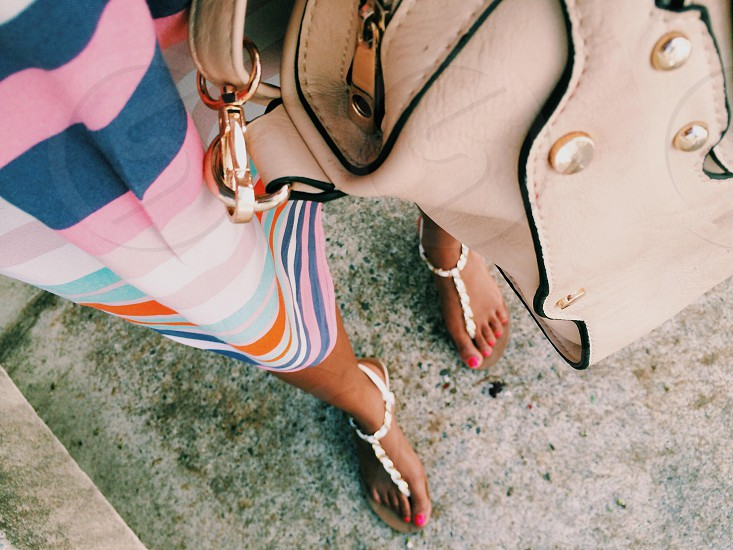 woman wearing pink white and blue striped dress shirt with gray leather handbag photo