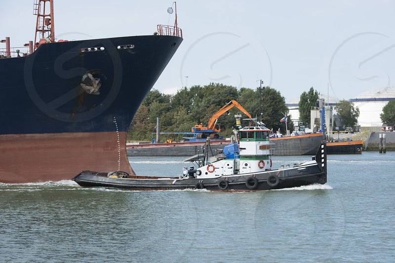 small tug boat relase the cables after pulling the big ship trough the maas river in Holland photo