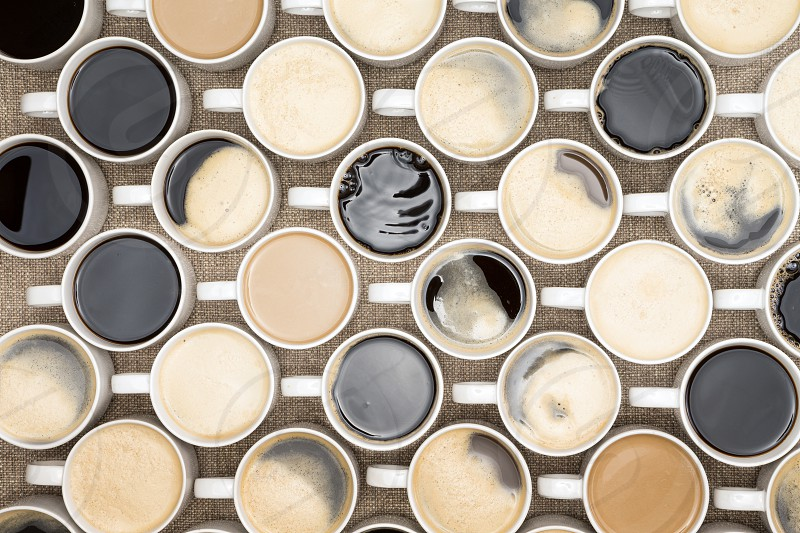 Conceptual image of regimented rows of coffee mugs lined up in straight rows with their handles facing the same direction like coffee soldiers overhead view with black espresso latte and cappuccino photo