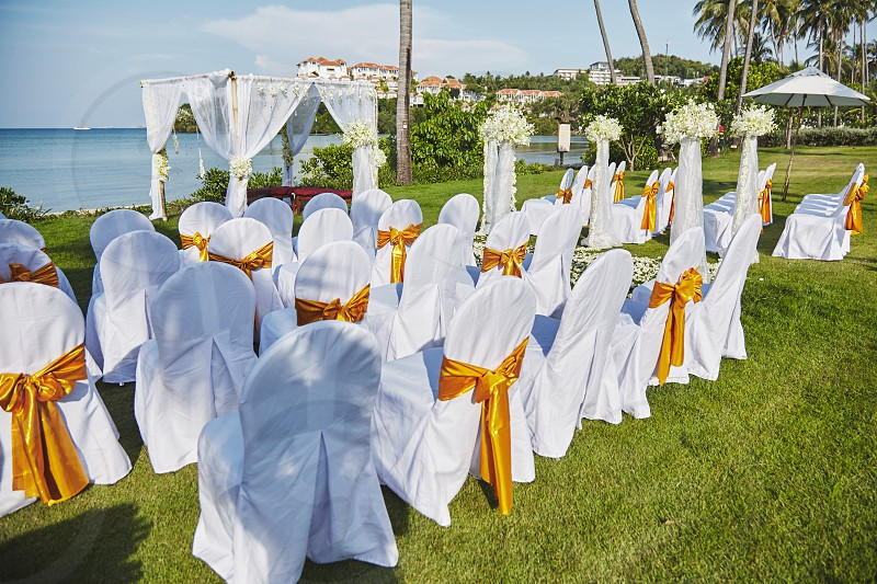 Rear view of the white chairs with gold sash organza lineup on beach wedding venue outdoors setting on green grass with panoramic sea view photo