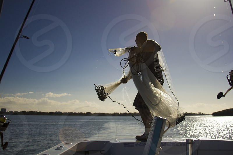 man throwing out fishing net from boat  photo