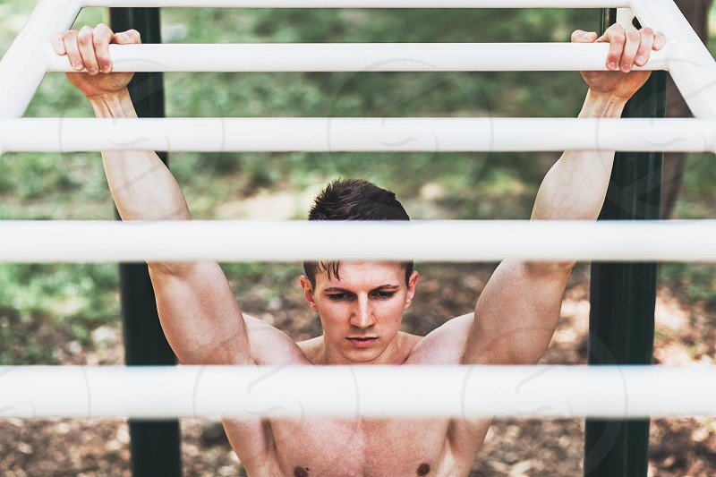 Muscular young man doing pull ups exercises on bar outside photo