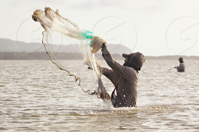 A fisherman standing in waste-deep water launches his fishing net into the sea hoping to catch fish. photo