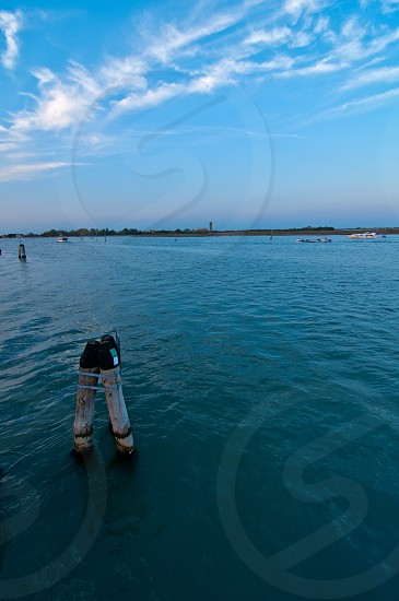 """Venice Italy lagune view with """"bricole"""" timber planted to sign the way of the canal photo"""