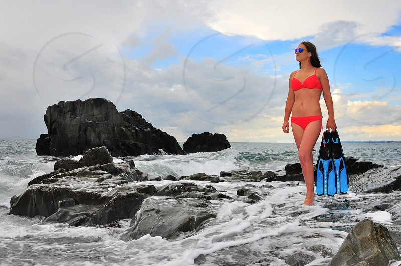 woman in red bikini standing and holding black and blue flipper shoes photo