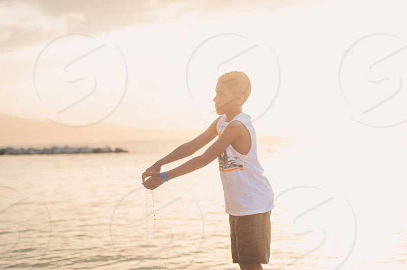 boy in white tank top and black shorts near sea photo