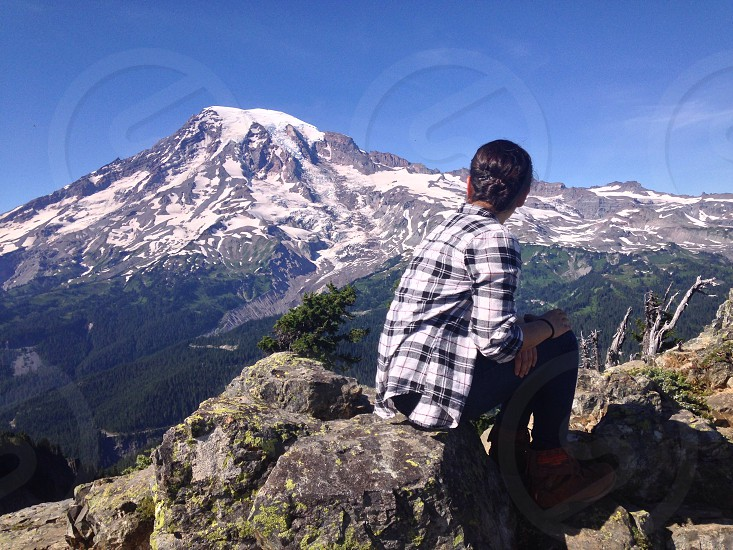 person in white and black plaid sport shirt and black pants sitting on rock with overview of snow coated mountain photo taken during daytime photo