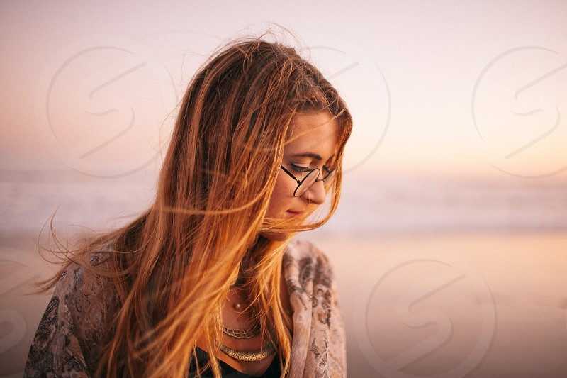 woman wearing white and gray floral top with black framed eyeglasses on seashore during golden hour photo