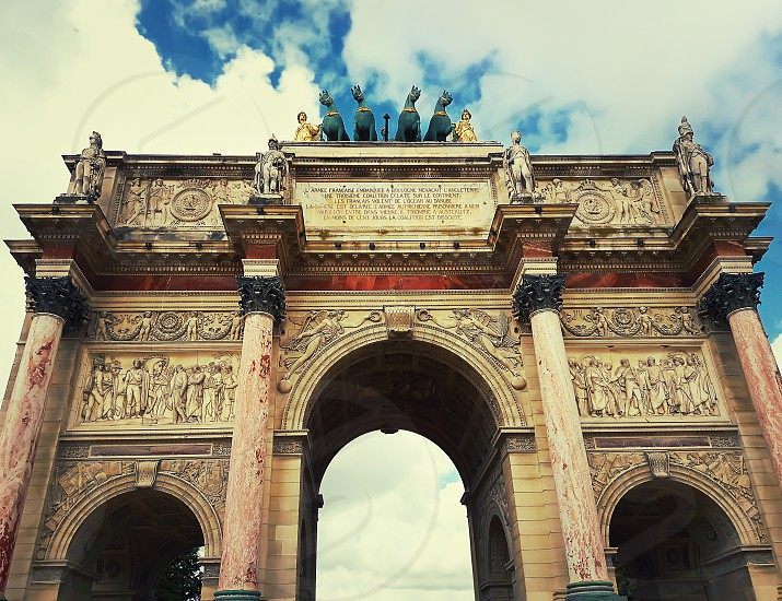 Close up view of the Triumphal Arch (Arc de Triomphe du Carrousel) located between Louvre and Tuileries Garden (Jardin des Tuileries) in Paris France. photo