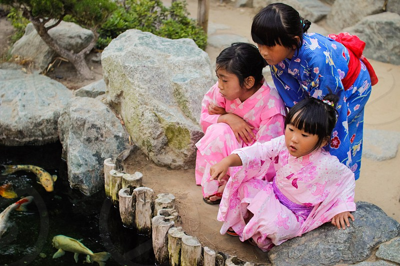 3 girls in kimono looking on fish pond during daytime photo