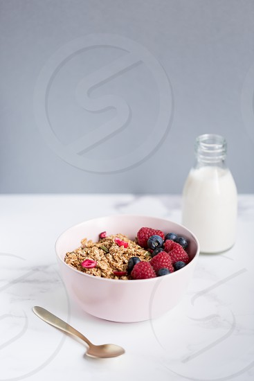 Healthy bowl of granola with raspberries and blueberries in a pink bowl with gold spoon and milk bottle. photo
