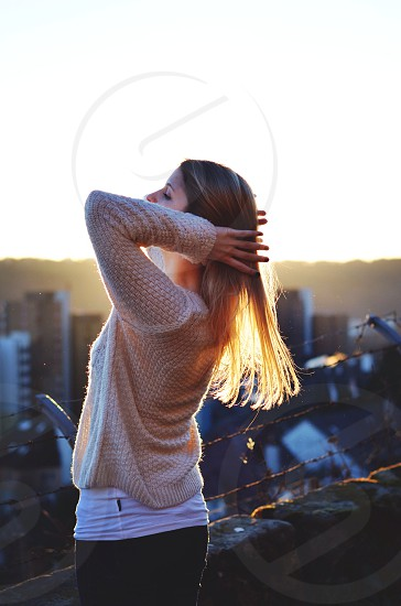 woman on top of building with sunrise photo