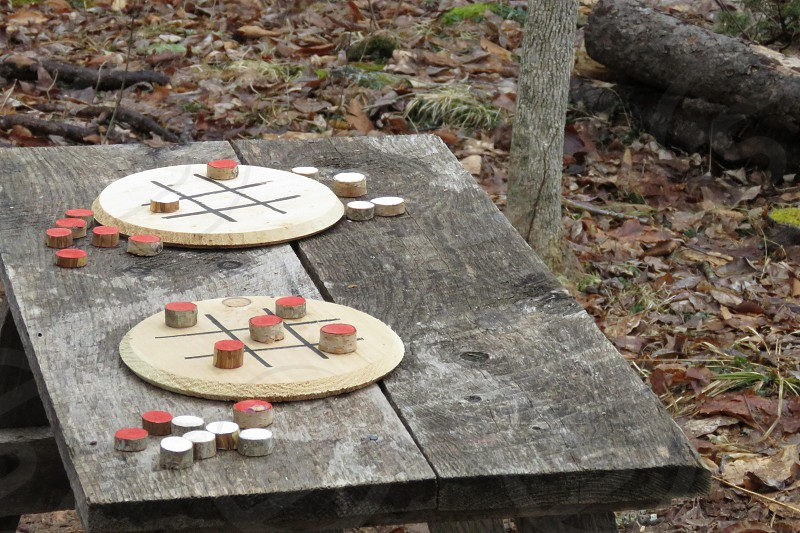 A set of circular game boatds with round game pieces on an old table. photo