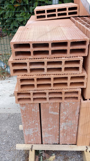 brown clay hollow blocks stacked near green metal mesh fence photo