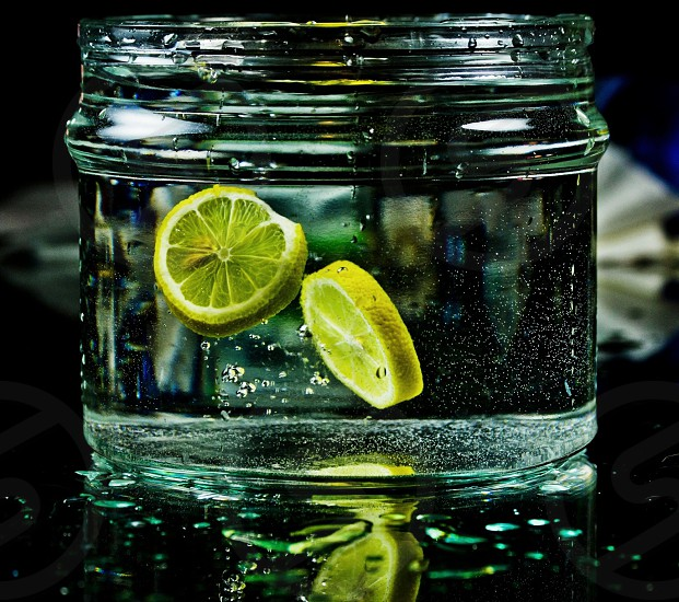 Yellow sliced citrus in clear jar glass photo
