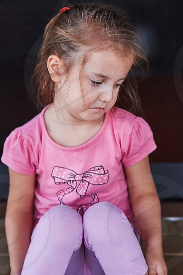 Little sad girl crying because of lost her toy sitting on a step on the patio. Real people authentic situations photo